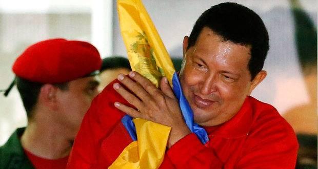 Hugo Chávez hugs national flag while celebrating re-election in October